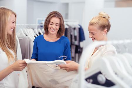 garments: Three attractive young female friends in a clothing store smiling as they discuss the selection of garments for sale Stock Photo