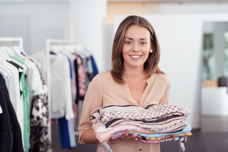 sales assistant: Half Body Shot of a Pretty Young Woman Holding Folded Clothes Inside the Clothing Store. Stock Photo