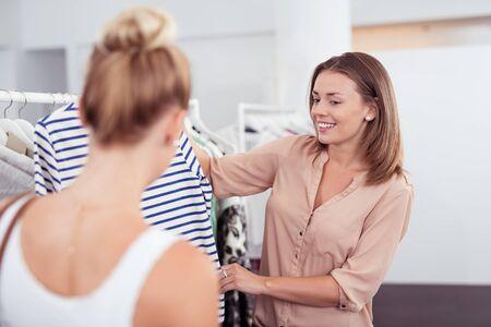 tienda de ropa: Dos jóvenes de sexo femenino Mejores amigos en busca de la camisa ocasional Dentro de una tienda de ropa