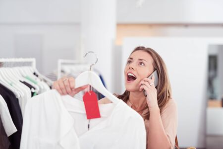 woman clothes: Young Woman Talking on Mobile Phone While Looking for Shirt Inside a Clothes Store, Showing Surprise Facial Expression. Stock Photo