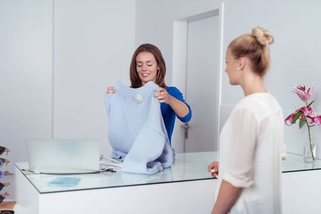 saleslady: Shop assistant folding a garment for a female customer standing at the checkout counter with a friendly smile