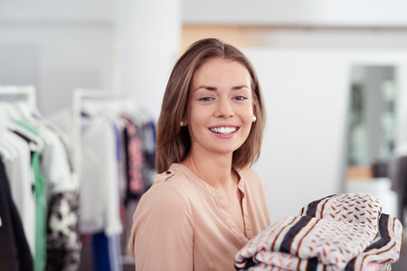 merchandise: Close up Happy Young Woman Looking at the Camera with Toothy Smile inside a Clothing Store.