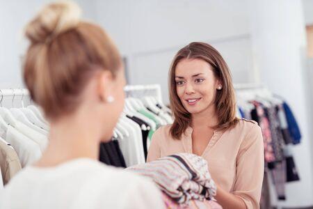tienda de ropa: Joven Mujer Shopper Hablando con una señora de ventas Mientras que la celebración de ropa interior de una tienda de ropa. Foto de archivo