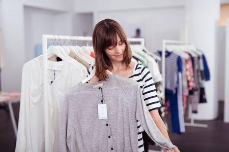 ropa de verano: La mitad Shot cuerpo de una mujer con estilo adulto que mira el gris manga larga camisa en una percha dentro de una tienda de ropa