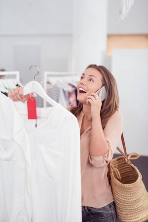 half body: Half Body Shot of a Happy Young Woman Receives Good News on Phone While Looking for Shirt inside a Clothing Shop. Stock Photo
