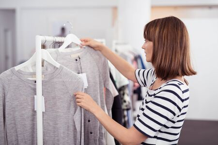 hanged woman: Half Body Shot of a Young Woman Looking for Casual Shirt with Good Quality Hanged on Rail Inside a Clothing Store
