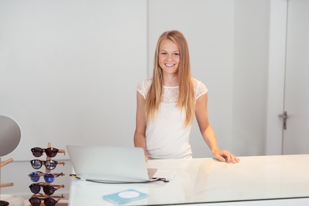 selling service smile: Pretty Blond Girl Smiling at the Camera While Standing at the Counter with Laptop Inside a Retail Fashion Store.