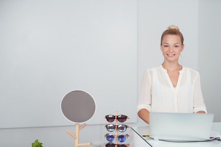 saleslady: Pretty Young Woman at the Counter with Laptop Computer Against White with Copy Space Inside a Retail Fashion Store.