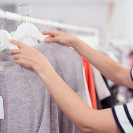 gray clothing: Close up Hands of a Woman Rummaging Trendy Clothes Hanging on the Rail Inside a Clothing Store Stock Photo
