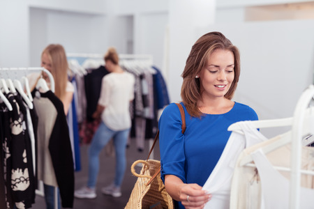 Stylist: Mujer bonita joven Shopper Comprobación de la calidad de la camisa de suspensión en un estante dentro de la tienda