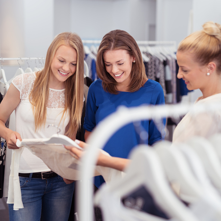 clustered: Three women friends choosing new clothes in a clothing store or fashion boutique clustered around a white summer top on a hanger smiling and chatting