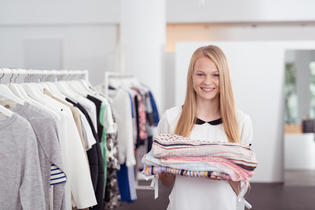 selling service: Half Body Shot of a Pretty Blond Girl Smiling at the Camera While Holding Some Folded Clothes Inside a Department Store