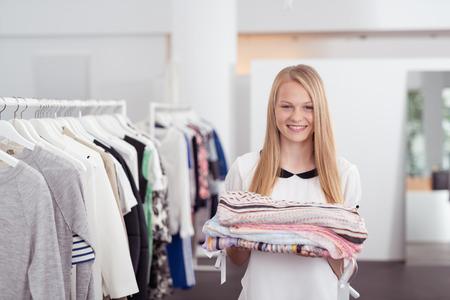 tienda de ropa: La mitad Shot Cuerpo de una chica rubia bastante sonriente a la c�mara mientras mantiene Algunos ropa doblada Dentro de una tienda por departamentos