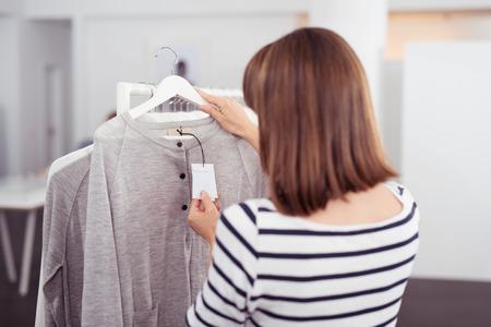 cheque en blanco: Primer plano de visión trasera de una mujer mirando la etiqueta de precio de una camisa de moda gris colgado en el carril interior de la tienda de ropa.