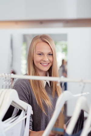clothes rail: Close up Pretty Blond Young Woman Standing Behind Clothes Rail Inside a Clothing Store and Smiling at the Camera Stock Photo