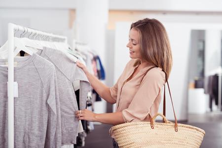 ropa colgada: La mitad Shot cuerpo de un Feliz mujer joven con el bolso de hombro mirando la ropa que cuelgan en el carril interior de la tienda de ropa.