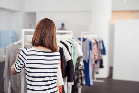 saleslady: Rear View of a Stylish Young Woman Looking at Trendy Clothes Hanged on Rail Inside the Department Store.