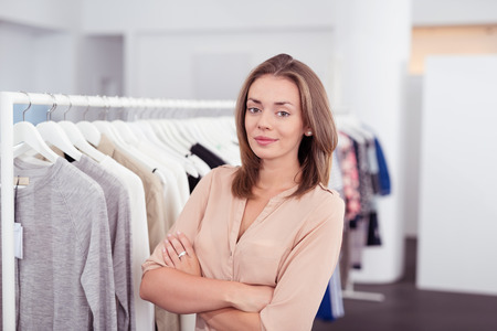 saleslady: Half Body Shot of a Confident Pretty Young Woman inside a Clothing Store, Smiling at the Camera with Arms Crossing Over her Stomach.