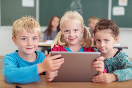 niños en la escuela: Tres pequeños niños lindos en jardín de niños que se sientan en un escritorio juntos compartiendo un equipo Tablet PC y mirando a la cámara con sonrisas tímidas