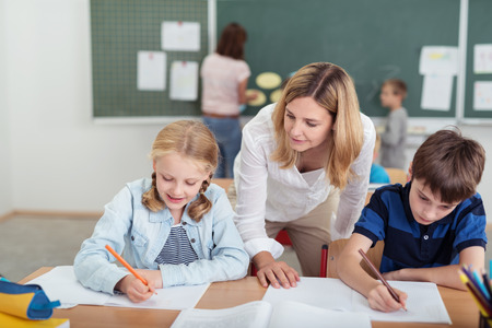 Teacher watching over a young boy and girl in class as they sit together at a desk writing notes with an open textbook in front of them Stock Photo