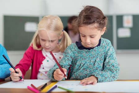 first day: Two cute young girls in primary school standing side by side drawing with colored pencils on sheets of paper