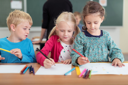 Three young children in kindergarten sharing a desk as they draw with colored pencils on sheets of paper, two little girls and a boy Stock Photo