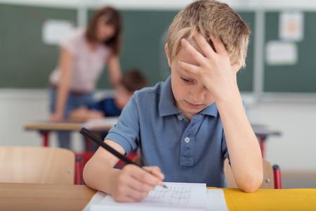 Jonge schooljongen hard aan het werk in de klas zit met zijn hoofd op zijn hand lezen en schrijven van notities op vellen wit papier