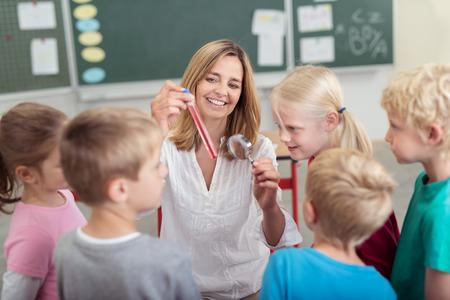 clases: Profesor de Química muestra una solución química en un tubo de ensayo a un grupo diverso de jóvenes escolares en la escuela primaria con una sonrisa feliz Foto de archivo