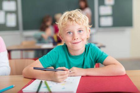 blonde yeux bleus: Heureux petit garçon en classe de maternelle assis à son bureau dessiner au crayon crayons de couleur et en regardant la caméra avec un sourire rayonnant