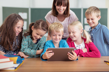 Female teacher with a diverse group of young pupils in class all smiling as they cluster around a tablet computer held by a young boy in the centre Stock Photo