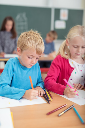 elementary school: Young boy sitting at a desk sketching with colored pencil crayons during art class in primary school with a little girl working alongside and teacher behind