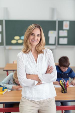 salle de classe: Sourire confiant femme enseignante attrayante appuy� contre un bureau dans la salle de classe, les bras crois�s que les �l�ves travaillent en arri�re-plan Banque d'images