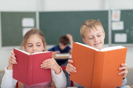 salle de classe: Deux jeunes �coliers, un gar�on et une fille, assis c�te � c�te � un bureau dans la lecture en classe de manuels