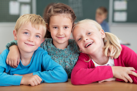 elementary age girl: Three happy young friends in kindergarten with a young girl in the centre standing with her arms around the shoulders of a boy and girl as they smile at the camera