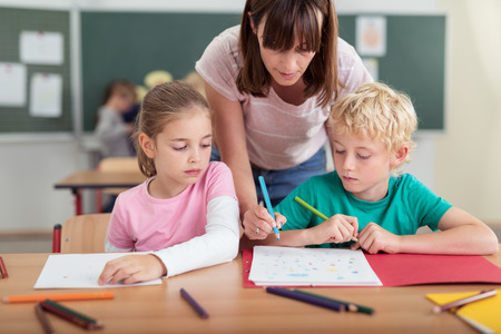 kindergarten education: Teacher helping two small kids in the classroom as she leans over them to write something on the little boys work, both children watching with solemn faces Stock Photo