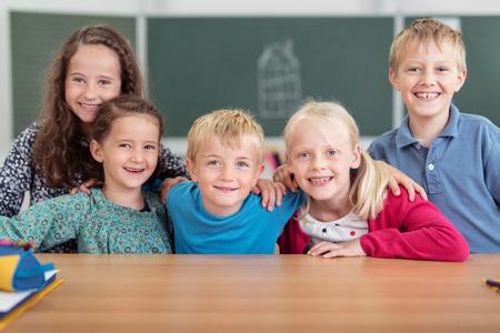 niños riendose: Grupo de alumnos sonrientes felices en la escuela primaria posando cogidos del brazo en una fila en un escritorio mirando a la cámara, niños y niñas Foto de archivo