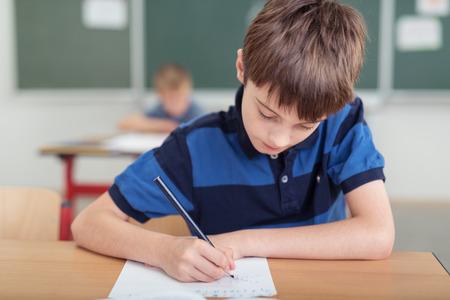 Giovane ragazzo prendere appunti in classe a scuola chinarsi suo lavoro di ufficio come lavora, lavagna e studenti in background Archivio Fotografico