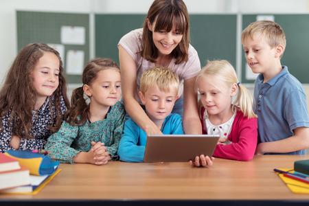 vzdělávací: Žena Učitel Výuka něco, co se děti pomocí počítače tablet Uvnitř třídě. Reklamní fotografie