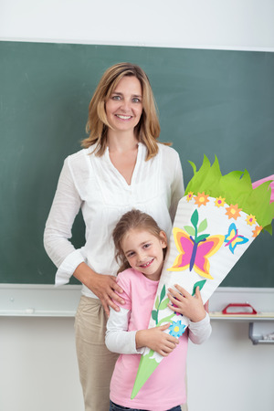 school class: Female Teacher with her Cute Student Hugging her Artwork, Smiling at the Camera Against Green Chalkboard.