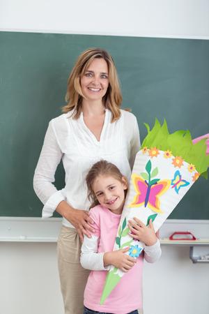 profesor alumno: Profesor de sexo femenino con su linda estudiante que abraza sus ilustraciones, sonriendo a la cámara contra la pizarra verde.
