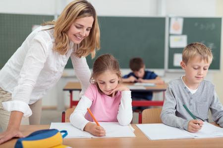 Glimlachend aantrekkelijke vrouwelijke leerkracht de controle op een kleine meisjes werken als ze zit naast een kleine jongen die op een bureau in de klas Stockfoto - 44358370