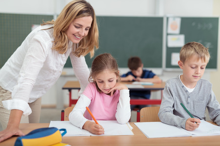 Smiling attractive female teacher checking on a little girls work as she sits alongside a small boy working at a desk in the classroom Stock fotó