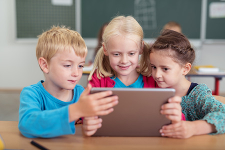 working on computer: Three young children sharing a tablet computer reading information on the screen as they sit at a desk in the school classroom Stock Photo