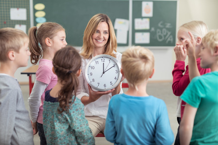 Female teacher teaching a class the time sitting on a chair holding a clock and smiling as a young girl offers to answer the question