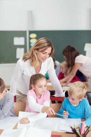 escuela primaria: Dos profesores que trabajan en una escuela primaria con una clase de niños pequeños que les ayude con su trabajo de clase, se enfocan a una profesora con un niño pequeño y una niña