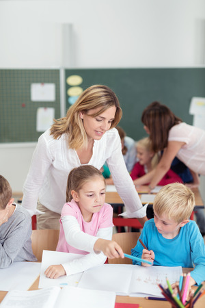 Two teachers working in a primary school with a class of young children helping them with their class work, focus to a female teacher with a small boy and girl Stock Photo