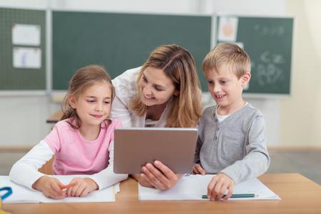 niños en la escuela: Profesor que muestra una tableta de dos jóvenes estudiantes inclinándose entre el niño y niña por detrás con una sonrisa como la sentada en su escritorio Foto de archivo