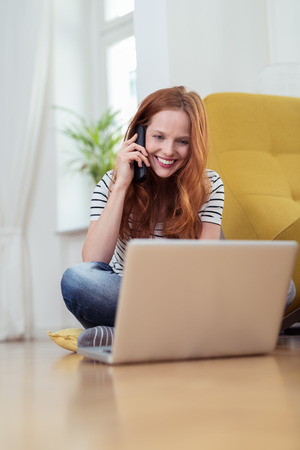 working at home: Smiling happy pretty young redhead woman talking on her mobile as she sits on the floor at home working on her laptop computer