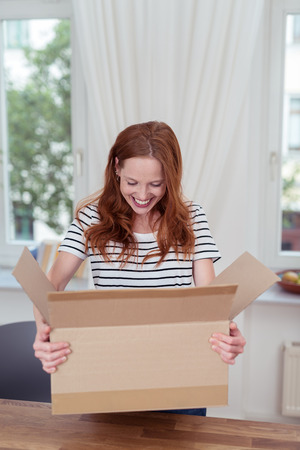 Happy Young Woman Carrying a Carton Box Over a Wooden Table and Looking What is Inside. Stock Photo