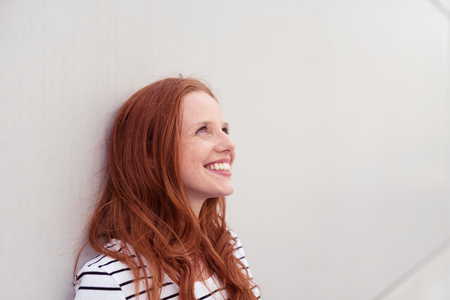 mujer sola: Close Up Mujer Rubia Pensativa Feliz Apoyándose Contra La Pared Blanca Y Mirando Para Arriba Con Sonrisa Dentuda. Foto de archivo